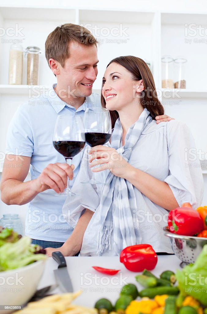 Affectionate couple drinking wine while cooking royalty-free stock photo