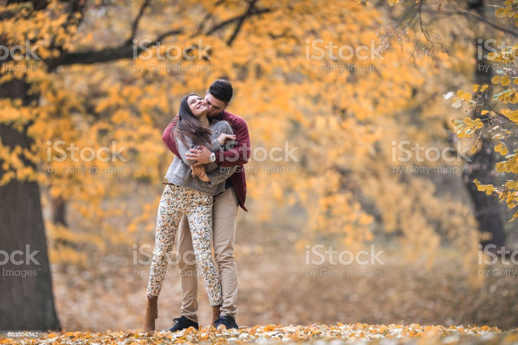Affectionate couple enjoying in their love during autumn day in the forest. stock photo