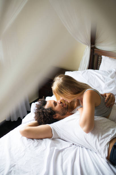 Affectionate couple enjoying weekend in bed stock photo