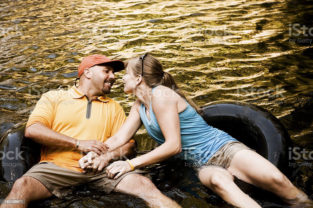 Affectionate Couple Floating on Inner Tubes royalty-free stock photo