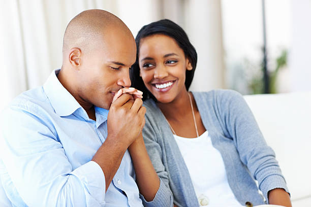 Affectionate couple having good time Affectionate African American couple having good time together at home kissinghand stock pictures, royalty-free photos & images