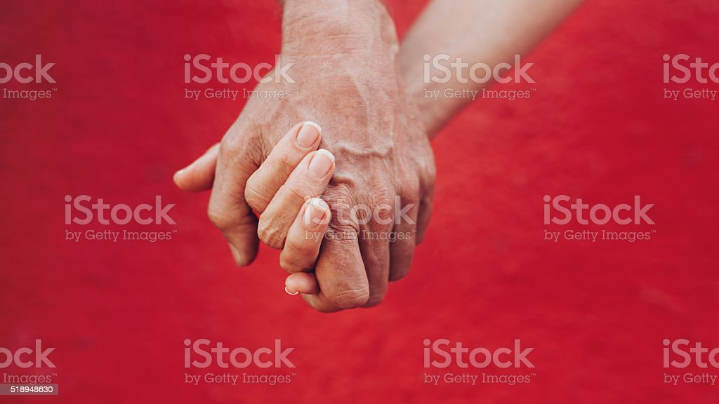 Close up of man and woman holding hands against red background....