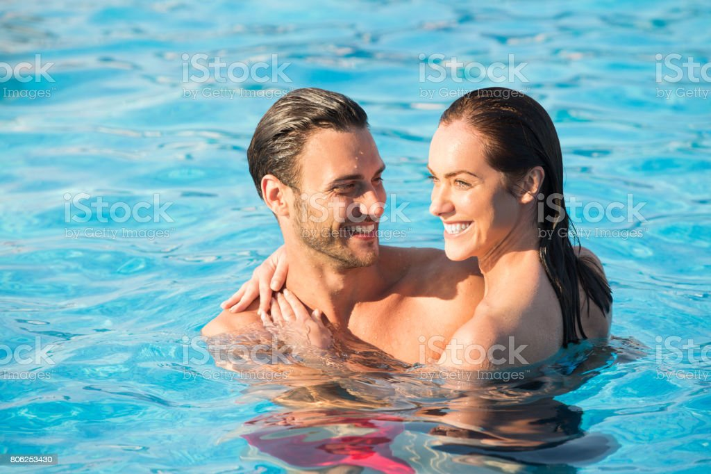 Affectionate couple in swimming pool stock photo