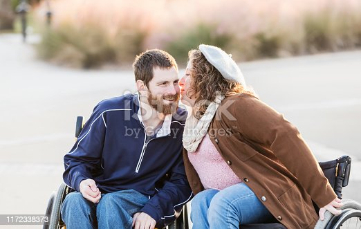 An affectionate couple in wheelchairs, side by side, outdoors. The woman is leaning over to give her boyfriend a kiss. The young woman, in her 20s, has spina bifida and her mate, a mid adult man in his 30s, has cerebral palsy.
