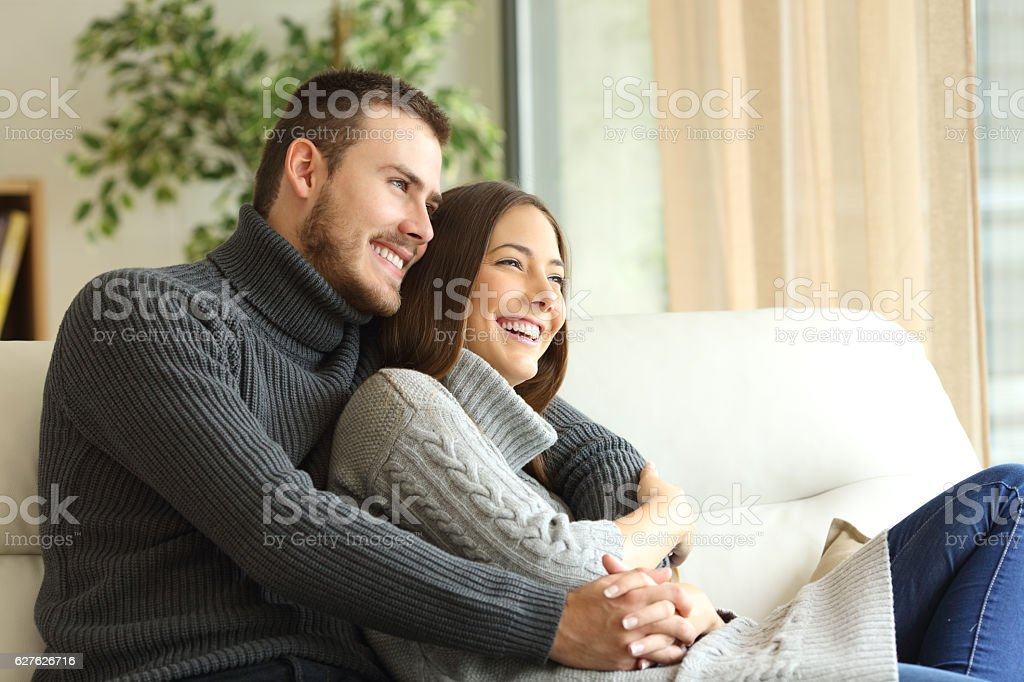 Affectionate couple resting at home stock photo