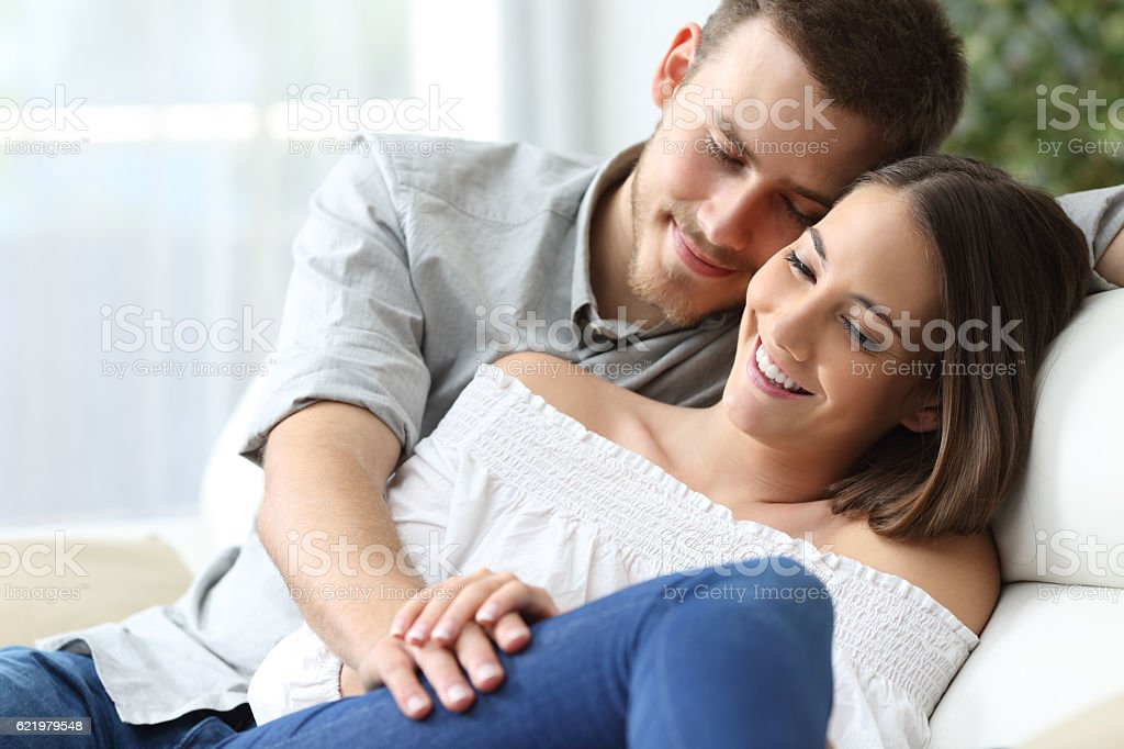 Affectionate couple sitting on a couch stock photo