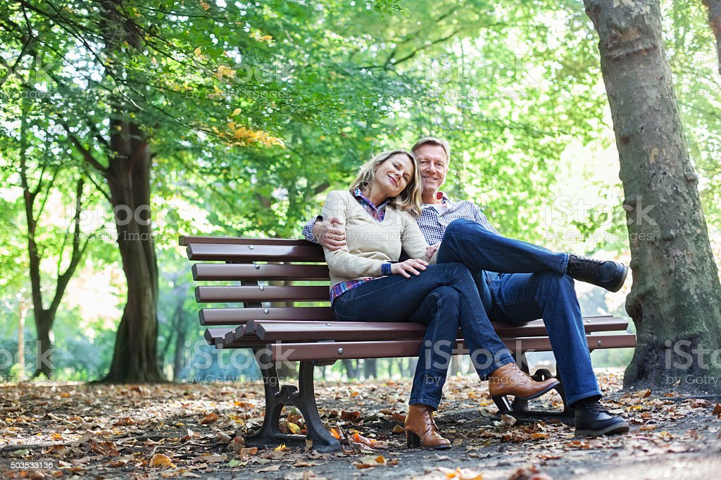 Affectionate  couple sitting on a park bench stock photo
