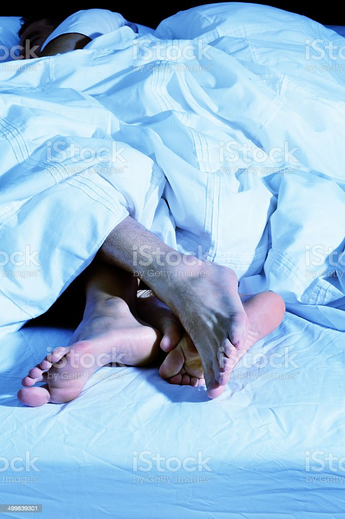 Affectionate couple's feet fondling each other in bed stock photo