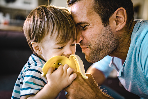 istock Affectionate father feeding his small boy with banana. 1096849590