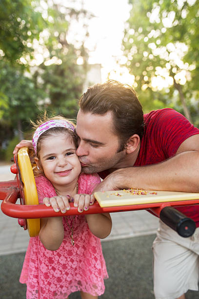 Affectionate father kissing his small daughter in the cheek outd Loving father kissing his little girl while spending a day in the park. Girl is looking at the camera. little girl kissing dad on cheek stock pictures, royalty-free photos & images