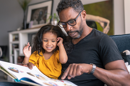 A loving father of African descent sits on the couch at home and reads a storybook to his preschool age daughter. The child is sitting on her father's lap and is smiling while looking at the book.