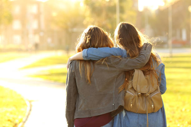 czuła przyjaciele chodzący o zachodzie słońca w parku - dwie osoby zdjęcia i obrazy z banku zdjęć