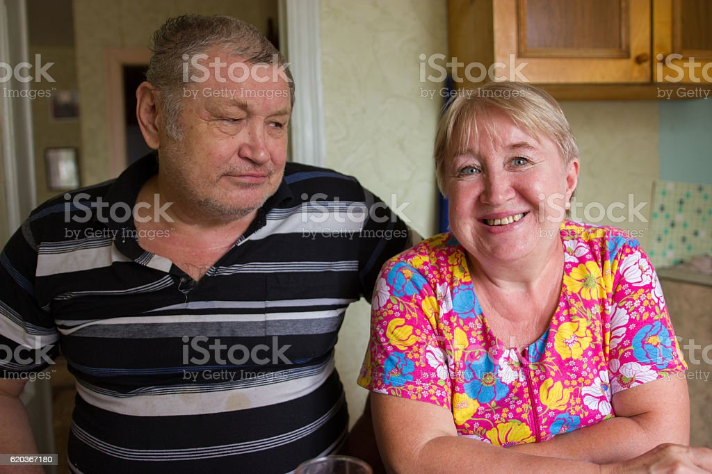 Affectionate grandparents having rest on kitchen at home, family concept zbiór zdjęć royalty-free