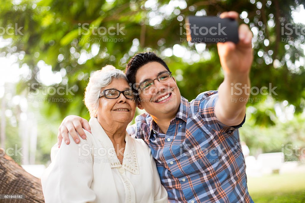 Affectionate grandson and grandmother taking a selfie – Foto