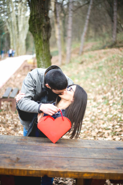affectionate guy kissing his girlfriend while giving her present outside - brunette woman eyeglasses kiss man foto e immagini stock