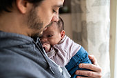 Young modern father embracing newborn baby boy at home on day