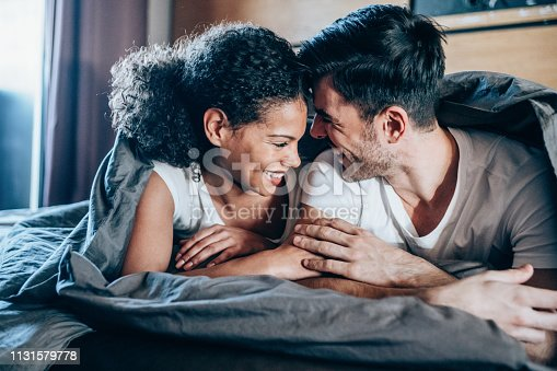 Happy young couple in bed in the morning