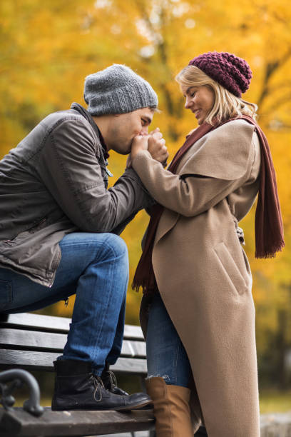 Hombre cariñoso de besos las manos de la novia en el parque durante el otoño. - foto de stock