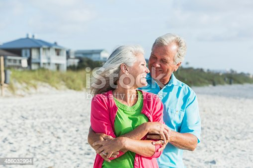 510491454 istock photo Affectionate mature couple standing on beach 486032994