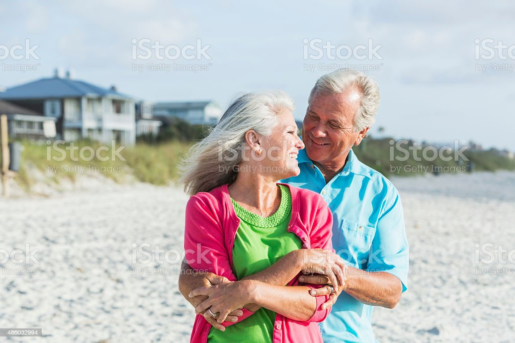 Affectionate mature couple standing on beach stock photo