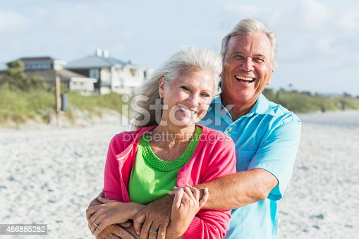 510491454 istock photo Affectionate mature couple standing on beach 486885282