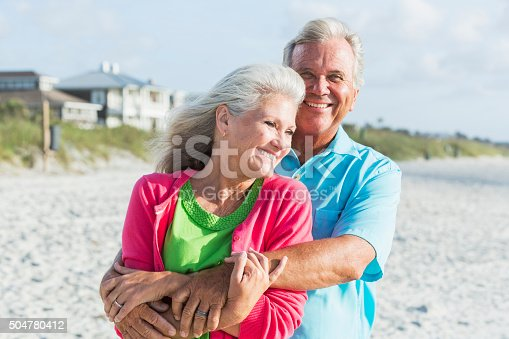 510491454 istock photo Affectionate mature couple standing on beach 504780412