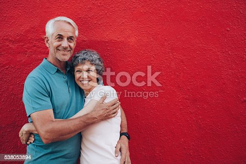 529076288 istock photo Affectionate mature couple together on red background 538053894