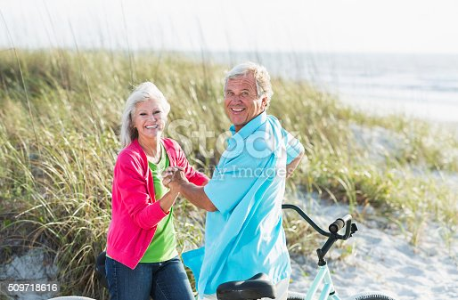 959016450 istock photo Affectionate mature couple with bikes at beach 509718616