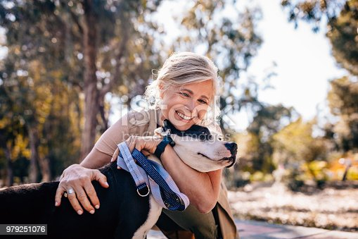 Happy senior woman enjoying walk in nature and embracing pet dog in forest park