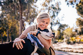 istock Affectionate mature woman embracing pet dog in nature 979251076