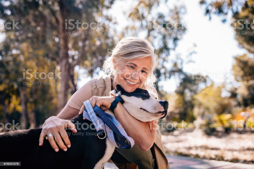 Affectionate mature woman embracing pet dog in nature stock photo