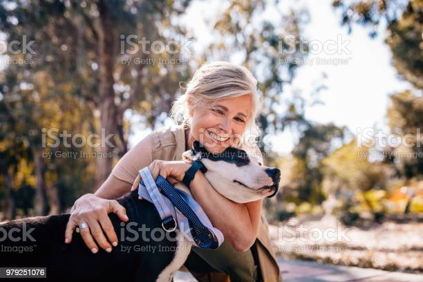 Photo of Affectionate mature woman embracing pet dog in nature