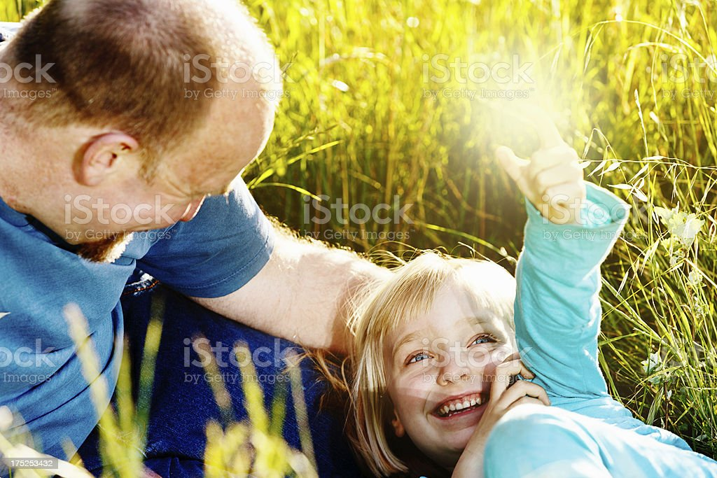 Affectionate moment between dad and daughter playing in sunshine stock photo