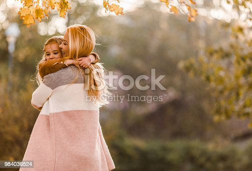 466231012istockphoto Affectionate mother and daughter enjoying in their hug at the park. 984036524