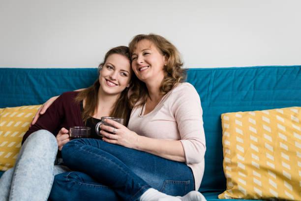 Liebevolle Mutter und Tochter sitzen zu Hause auf sofa – Foto