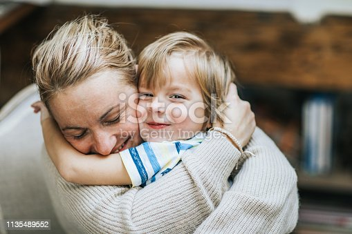Happy mother embracing her small son at home, while boy is looking at camera.