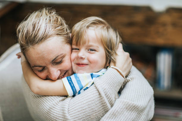 Affectionate mother and son embracing at home. Happy mother embracing her small son at home, while boy is looking at camera. mother and child stock pictures, royalty-free photos & images