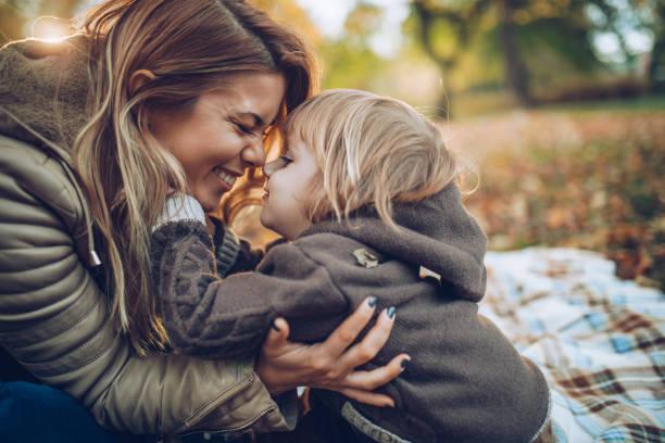 Liebevolle Mutter und Sohn Spaß beim reiben ihre Nasen in der Natur. – Foto