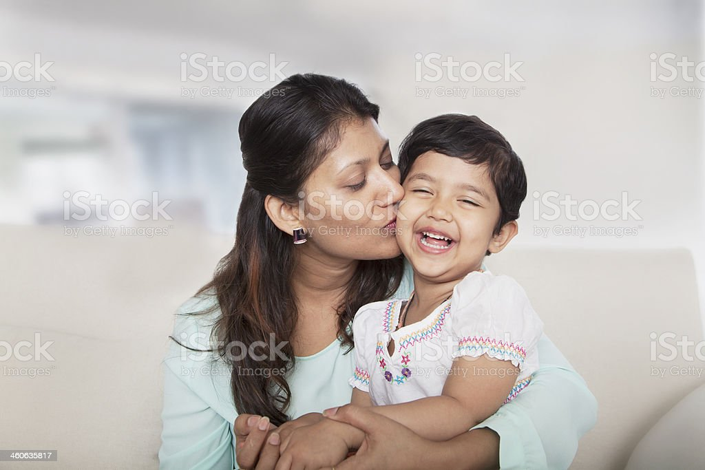 Affectionate mother holding and kissing her daughter on the couch stock photo