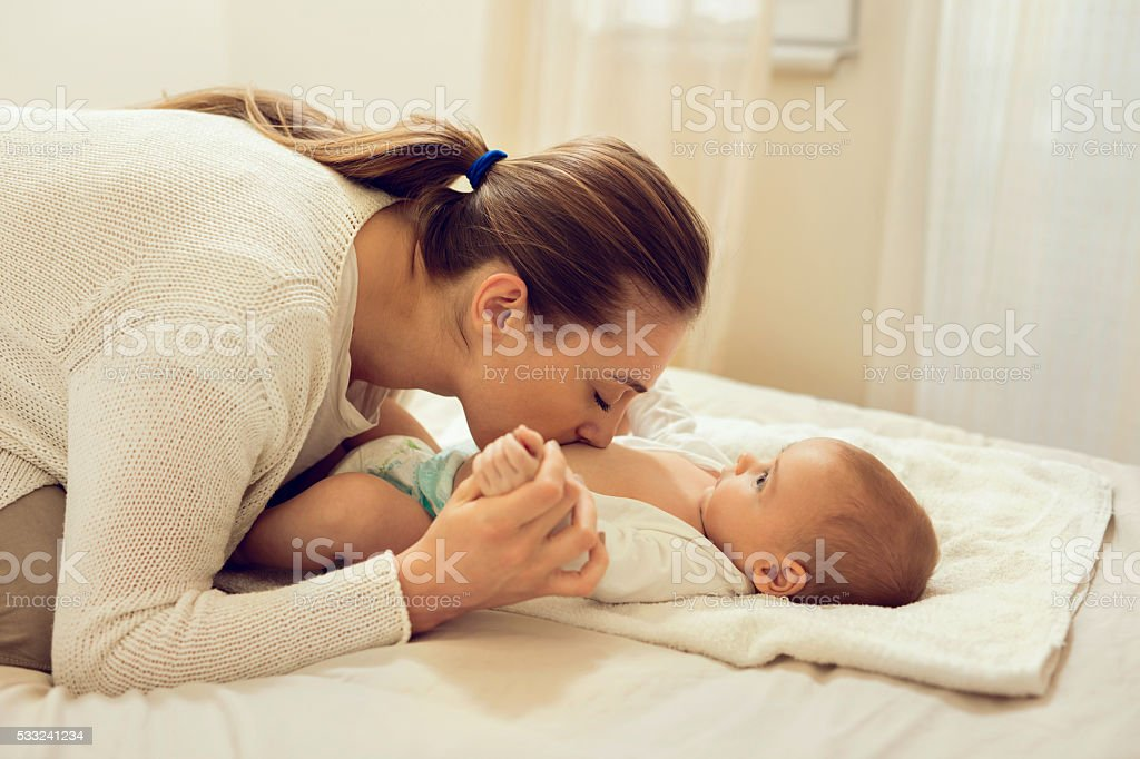 Affectionate mother in bedroom kissing baby's belly. stock photo