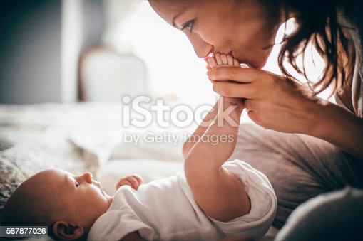 A happy mother kisses her baby's feet while she is lying down. The baby is looking up at her wearing a white baby grow.
