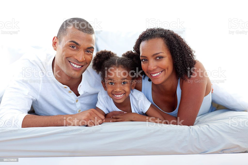 Affectionate parents and their daughter smiling at the camera royalty-free stock photo