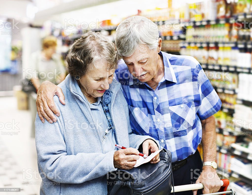 Affectionate senior couple check shopping list in supermarket royalty-free stock photo