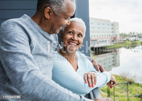 A senior African-American couple standing on a balcony overlooking the water. They are looking lovingly into each other's eyes, smiling.