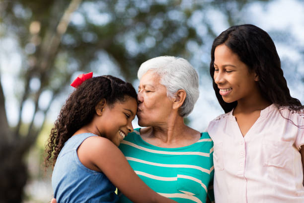 Affectionate senior woman embracing and kissing granddaughters stock photo