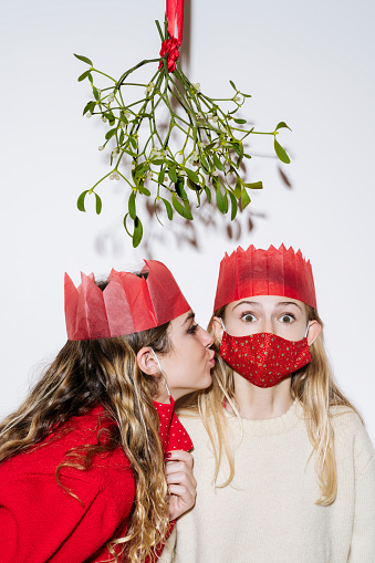 Partial view of teenage sisters in Christmas cracker hats, casual sweaters, with and without protective masks struggling with tradition in time of COVID-19.