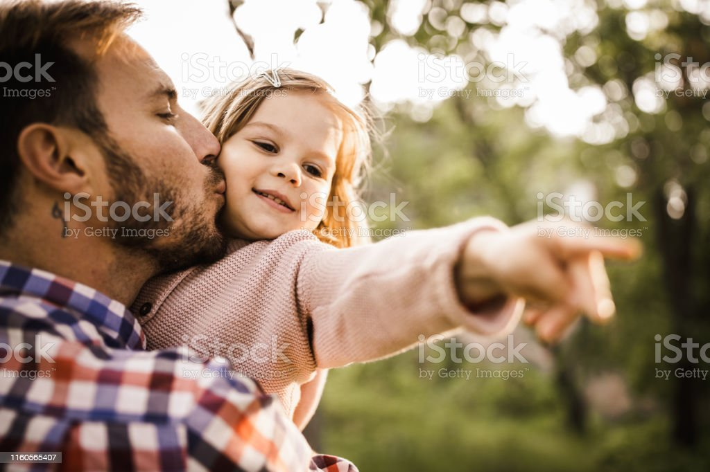 Loving single father kissing his small girl during spring day at the...