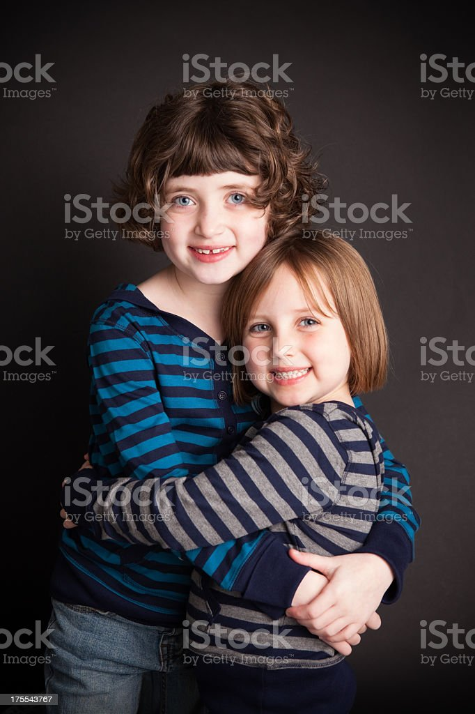 Affectionate Sisters Hugging Each Other, With Black Background royalty-free stock photo