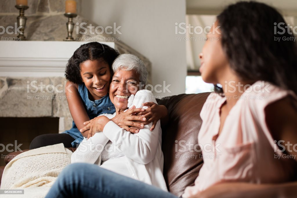 Affectionate teen granddaughter hugging her grandmother at home - Royalty-free 12-13 Years Stock Photo