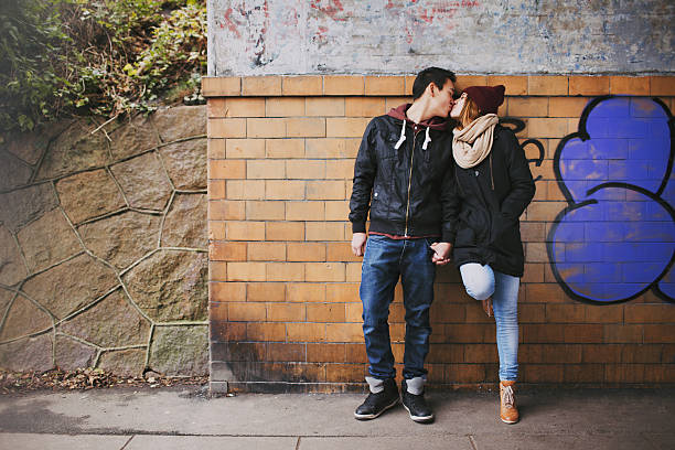 Affectionate teenage couple kissing on street Affectionate teenage couple kissing outdoors against a wall on street. Mixed race couple in love. cute teen couple stock pictures, royalty-free photos & images
